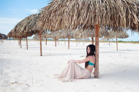 Young attractive woman on vacation at the sea, sitting on the sand under a straw umbrella. The girl travels to the sea.