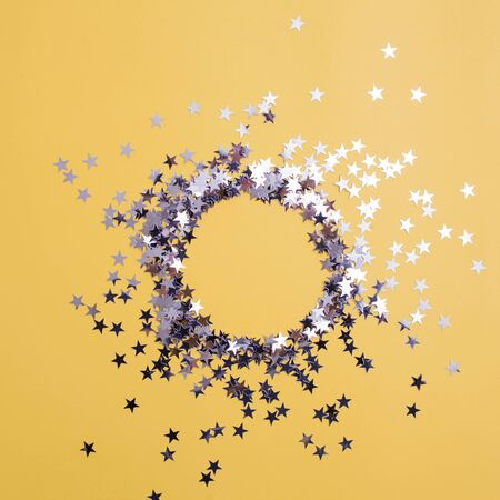 Star-shaped confetti scattered on a yellow background. Celebration and party, concept. Copy space, glitter in the shape of a circle, free space in the center