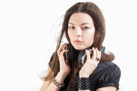 Young stylish woman in large headphones listening to music and having fun. Music lover girl with flying hair enjoys music