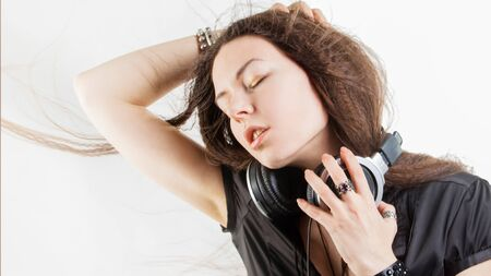 Young brunette woman in large headphones listening to music and having fun. Music lover girl with flying hair enjoys music Фото со стока