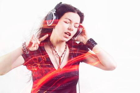 Girl fan sings and dances listening to music. Young brunette woman in big headphones enjoys music, double exposure, concept
