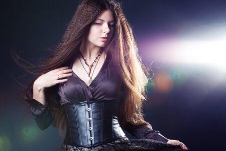 Mujer atractiva joven con el pelo largo como una bruja. Mujer morena, estilo fantasía mística. Chica en corsé y falda larga, bruja medieval