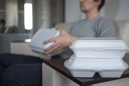 Food delivery service from cafes and restaurants. convenient habit for people who do not know how to cook. A man on the couch resting and going to eat