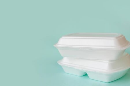 Food delivery service from cafes and restaurants. Food containers on light blue background, copy space