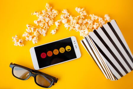 A white smartphone with smilies on the screen, 3d glasses, a black-and-white striped paper box and scattered popcorn are lying on a yellow background. critics rating and the audience, concept