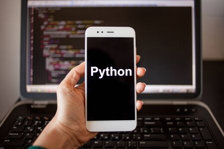 Mobile application development, Python programming language for mobile development. Smartphone in hand with the inscription Python on the screen