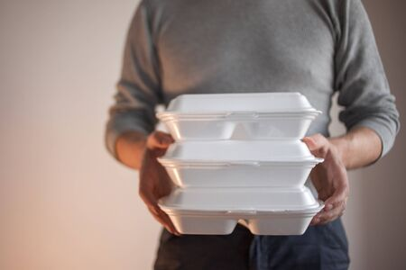 Food delivery. Delivery of tasty and healthy dishes. A man holding a box with several portions.