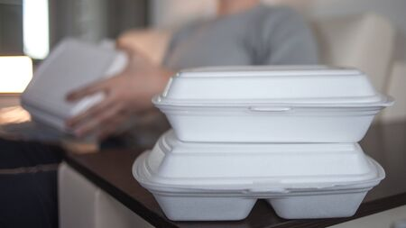 Food delivery service from cafes and restaurants. A man on the couch resting and going to eat. Food containers in the foreground Stok Fotoğraf