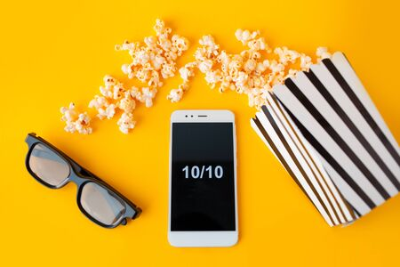 A white smartphone with smilies on the screen, 3d glasses, a black-and-white striped paper box and scattered popcorn are lying on a yellow background. Top vew. Stock Photo