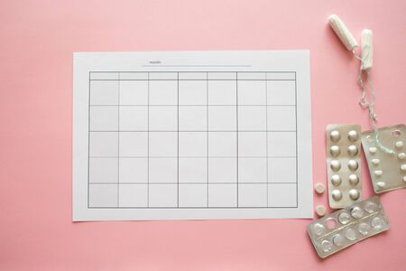 PMS and the critical days concept. Blank monthly calendar for menstrual, PMS or ovulation marks.Pain pills and personal care products, pink background