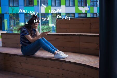 Young girl, student, brunette with long hair in jeans and white sneakers, with a phone in her hand, crying, covering her face with her hands, sitting with legs on a wooden bench, the stairs in the campus. Offensive words fly out of the phone.