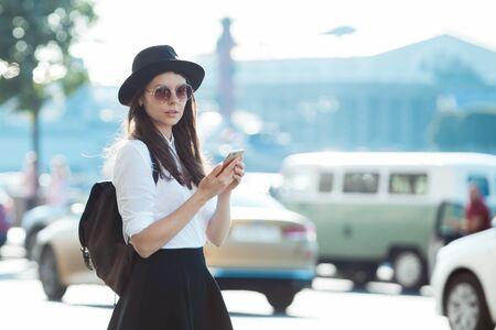 young woman in a hat and with a backpack walks in the city and uses a smartphone. Hipster on a walk uses the phone and takes photos for social networks