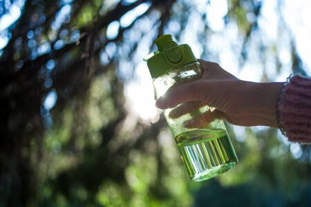 The hand holds a transparent sports glass bottle with a green cap, filled with clear water, against the background of trees and sky. Through the water you can see the landscape. Blurred background.