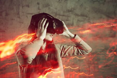 girl playing VR games, concept of modern technology, effect of double exposure. A young cheerful woman uses a virtual reality helmet. Deep dive into gaming reality, VR glasses