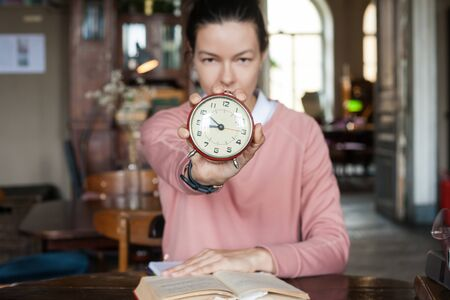 Deadline. A closeup alarm clock aimed at the frame held by a brunette girl in a pink sweater sitting among books at a table in an old library. Stockfoto - 130107117