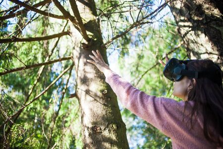 Virtual forest. A young woman among the trees, wearing virtual reality glasses, touches the boles and branches, the air, on a sunny summer day, straightens her helmet. Side and back view. Copyspace.