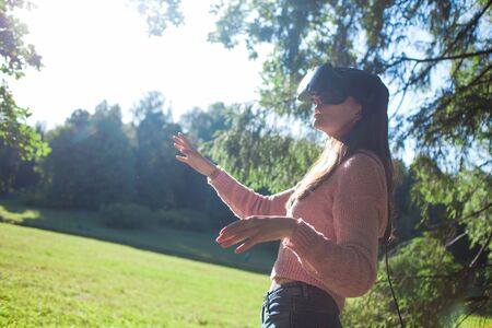 Virtual forest. A young woman in virtual reality glasses stands under the trees in a clearing, on a sunny summer day, touches the air with her hands, straightens her helmet. Side view. Copyspace.