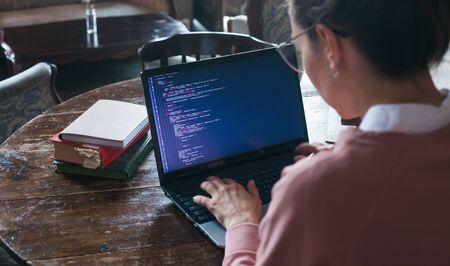 Système de piratage. Une fille excitée aux cheveux noirs et vêtue d'un pull rose et de lunettes écrit du code sur un ordinateur portable alors qu'elle est assise dans une bibliothèque. Travaillez sous couverture. Fille hacker. Vue depuis l'épaule. Banque d'images