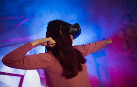 A young woman in virtual reality glasses, amid bright light and smoke, raised her hands in a combat pose. Shoots from an imaginary bow. View from the shoulder from the back. Imagens