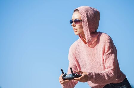 Young woman wearing sunglasses and hoodie holding a remote control, controls, controls are not visible in the frame drone. A woman carefully looks into the distance against a blue sky. Copyspace. Stock fotó