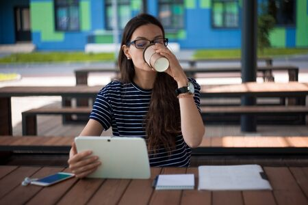 Young pretty brunette girl, student, using the tablet, drinking coffee, working online, using voice messages. On the table are a notebook for notes, a smartphone, wireless headphones. Outdoor.