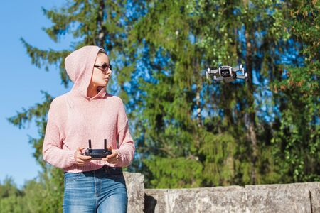A young woman in a pink hoodie and dark glasses holds, launches, catches the drone with one hand, and holds the control panel in the other. Outdor. Copyspace.