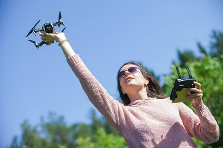 A young woman in a clearing in a park launches, checks, holds the drone with her outstretched arm above her head, in another control panel. Outdor. Copyspace. The woman is partially visible.