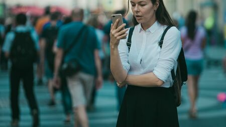 Girl on the street among the crowd of passers-by, photos in the style of surveillance. young woman in the city uses her phone to find a route, uses the Internet and mobile applications.