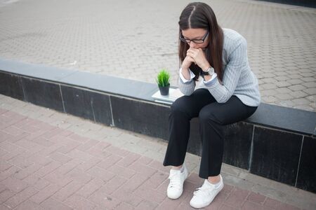 Dismissal from a large company. Economic crisis and problems with qualifications. A depressed young woman is sitting on the steps in front of the business center with her things.