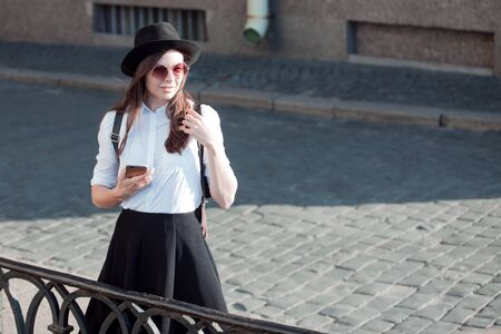 young woman in a hat and a white shirt walks in the city and uses a smartphone. Hipster on a walk uses the phone and takes photos for social networks