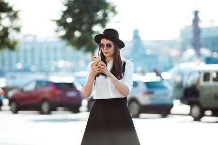 young woman in a hat and with a backpack walks in the city and uses a smartphone. Hipster on a walk uses the phone and takes photos for social networks Stockfoto