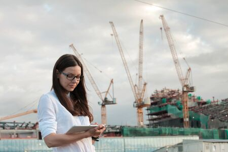 architect on the construction site makes supervision. Young woman engineer or a businessman in the field of development and construction