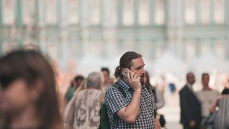 guy in a crowd on a big city street. A young bearded man in the city uses a mobile phone, talking on the phone, a business conversation.