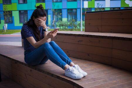 Młoda dziewczyna, studentka, brunetka z długimi włosami w dżinsach i białych tenisówkach, z telefonem w dłoni, płacząca, zakrywająca twarz rękami, siedząca nogami na drewnianej ławce, w kampusie,