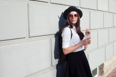 Young woman in hat walking in city. Girl tourist enjoys the walk. Hipster in a hat with a backpack, Drinking coffee smoothies. On wall background, copy space