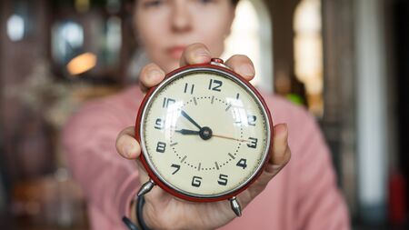 Deadline. A closeup alarm clock aimed at the frame held by a brunette girl in a pink sweater sitting among books at a table in an old library.