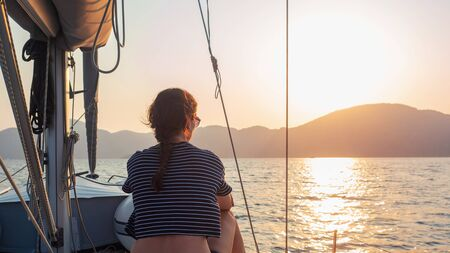 attractive young woman in a striped t-shirt enjoys the sunset on the deck of a sailing yacht. Sailing regatta, sea voyage. Free space on the right