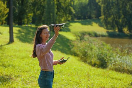 A young woman in a clearing in a park launches a drone, holding an aircraft in one hand and a control panel in the other. Outdor. Copyspace.