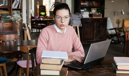 Exam preparation. Attractive brunette student girl in glasses and pink sweater, sits at a laptop, is engaged in an old library. Preparing for presentation. Piles of books are lying next to the table.