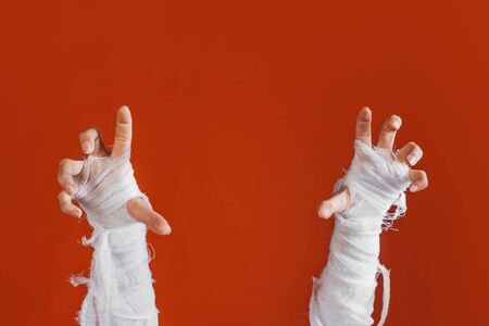 Halloween, costume image. The mummys hand in bandages making gestures. The hand of the risen dead reaches up from the bottom, a bright orange background. mummy attacks