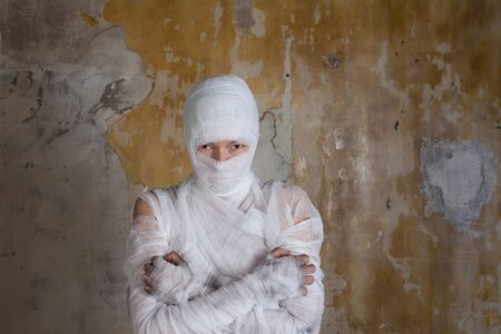 Halloween image, mummy in bandages, risen dead legendary character. young woman in the form of a mummy wrapped in bandages, against the textured old wall 版權商用圖片