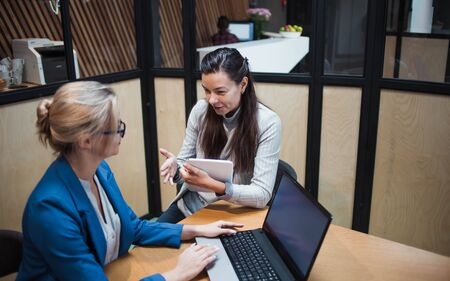 young HR woman interviews a candidate for a job. Business meeting two young women at work discussing the project. Interview with a Manager or job interview, portfolio review