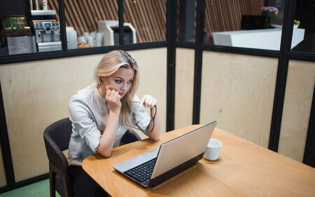 Tired overworked young woman in the office at the laptop. Office worker at the table, sitting clutching head