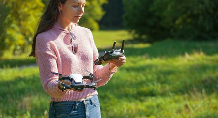 A young woman in a clearing in a park launches, checks, holds a drone, in one hand, in the other control panel. Outdor. Copyspace. Drone close up. The woman is partially visible. Banco de Imagens