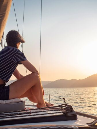 attractive young woman in a striped t-shirt enjoys the sunset on the deck of a sailing yacht. Sailing regatta, luxury vacation at sea. Free space on the right