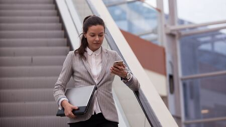 Young businesswoman with glasses and a phone in her hands. In the office or business center. Work and career, concept