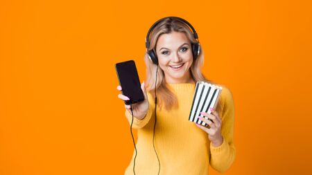 Cinema by subscription, concept. A young woman in a yellow sweater with headphones with a smartphone and popcorn in her hand. Watching movies and TV series on the streaming service. Stok Fotoğraf