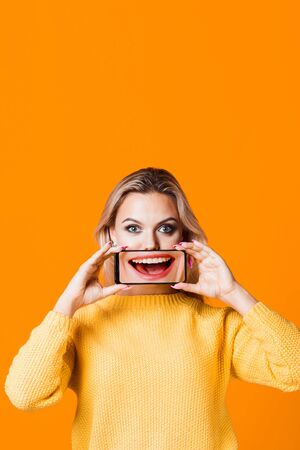 Voice assistant and online translator of foreign languages in your smartphone, concept. The girl with the phone, a smiling mouth on the screen ,yellow background Stok Fotoğraf