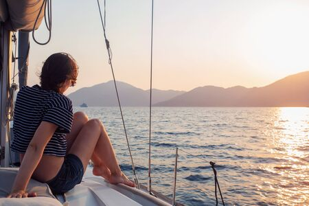 attractive young woman in a striped t-shirt enjoys the sunset on the deck of a sailing yacht. Girl yachtsman looks into the distance. Sailing regatta, sea voyage