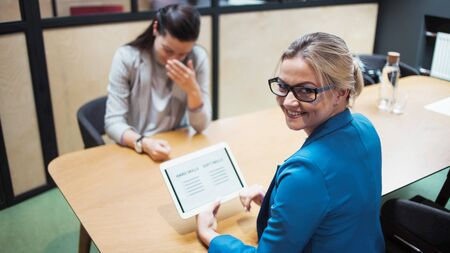 Job interview. The recruiter holds a tablet with a check list of the necessary skills of the candidate. Hard skills and soft skills, concept